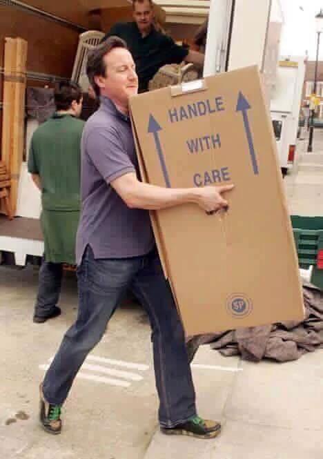 حقيقة صورة رئيس وزراء بريطانيا ديفيد كاميرون يحمل أمتعته