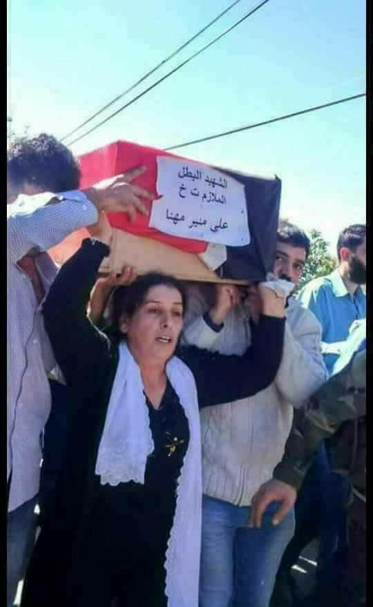 حقيقة صورة أم تحمل نعش ابنها الشهيد